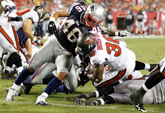 TAMPA, FL - AUGUST 18:  Running back Allen Bradford #38 of the Tampa Bay Buccaneers scores a touchdown as defender Niko Koutouvides #46 of the New England Patriots cannot stop him during a preseason game at Raymond James Stadium on August 18, 2011 in Tamp