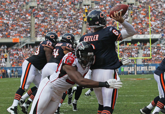 CHICAGO, IL - SEPTEMBER 11:  Jay Cutler #6 of the Chicago Bears is hit while throwing a pass from the end zone by Lawrence Sidbury #90 of the Atlanta Falcons at Soldier Field on September 11, 2011 in Chicago, Illinois. The Bears defeated the Falcons 30-12