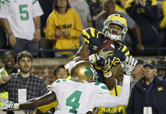 ANN ARBOR, MI - SEPTEMBER 10: Roy Roundtree #12 of the University of Michigan catches a 16 yard touchdown pass from Denard Robinson #16 late in the fourth quarter during the game against the Notre Dame Irish at Michigan Stadium on September 10, 2011 in An