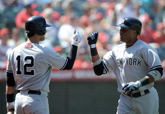 ANAHEIM, CA - SEPTEMBER 11:  Robinson Cano #24 of the New York Yankees celebrates his solo homerun with Eric Chavez #12 to trail 3-2 to the Los Angeles Angels of Anaheim during the fourth inning at Angel Stadium of Anaheim on September 11, 2011 in Anaheim