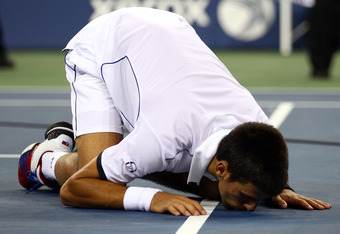 NEW YORK, NY - SEPTEMBER 12:  Novak Djokovic of Serbia lisses the court after he won match point against Rafael Nadal of Spain during the Men's Final on Day Fifteen of the 2011 US Open at the USTA Billie Jean King National Tennis Center on September 12, 2