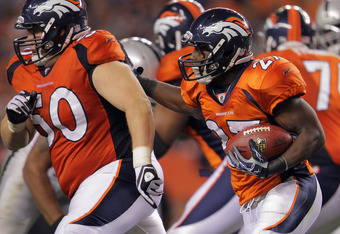 DENVER, CO - SEPTEMBER 12:  Running back  Knowshon Moreno #27 of the Denver Broncos follows the block of center J.D. Walton #50 of the Denver Broncos as he rushes against the Oakland Raiders at Sports Authority Field at Mile High on September 12, 2011 in