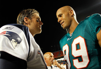 MIAMI GARDENS, FL - SEPTEMBER 12:   Tom Brady #12 of the New England Patriots talks with  Jason Taylor #99 of the Miami Dolphins after  a game  at Sun Life Stadium on September 12, 2011 in Miami Gardens, Florida.  (Photo by Mike Ehrmann/Getty Images)