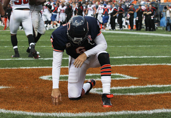 CHICAGO, IL - SEPTEMBER 11:  Jay Cutler #6 of the Chicago Bears takes a moment after being taken down after throwing a pass from the end zone by Lawrence Sidbury of the Atlanta Falcons at Soldier Field on September 11, 2011 in Chicago, Illinois. The Bears