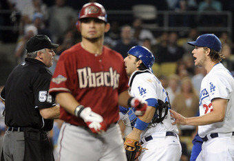 Dodgers pitcher Clayton Kershaw is ejected by Umpire Bill Welke as D'Backs left fielder Gerardo Parra takes his base.
