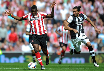 SUNDERLAND, ENGLAND - AUGUST 20: Asamoah Gyan of Sunderland in action with Jonas Gutierrez of Newcastle United during the Barclays Premier League match between Sunderland and Newcastle United at Stadium of Light on August 20, 2011 in Sunderland, England.