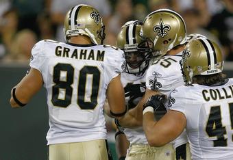GREEN BAY, WI - SEPTEMBER 8: Robert Meachum #17 of the New Orleans Saints celebrates with Jimmy Graham #18, David Thomas #85 and Jed Collins #45 after scoring a touchdown during the game against the Green Bay Packers at Lambeau Field on September 8, 2011