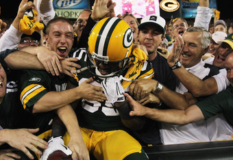GREEN BAY, WI - SEPTEMBER 08: Greg Jennings #85 of the Green Bay Packers is mobbed by fans after leaping into the stands following a touchdown catch against the New Orleans Saints during the NFL opening season game at Lambeau Field on September 8, 2011 in