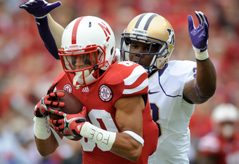 LINCOLN, NE - SEPTEMBER 17: Kenny Bell #80 of the Nebraska Cornhuskers hauls in a long pass over Quinton Richardson #28 of the Washington Huskies for the first play of their game at Memorial Stadium September 17, 2011 in Lincoln, Nebraska.  (Photo by Eric