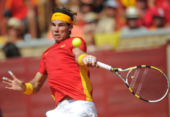 CORDOBA, SPAIN - SEPTEMBER 18:  Rafael Nadal of Spain plays a backhand to Jo-Wilfried Tsonga of France during the third and final day of the semi final Davis Cup match between Spain and France at the Plaza de Toros de los Califas on September 18, 2011 in