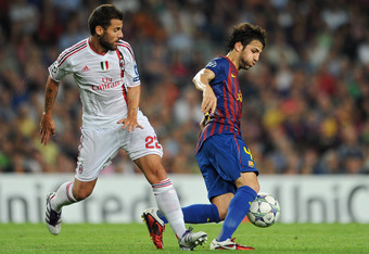 BARCELONA, SPAIN - SEPTEMBER 13: Cesc Fabregas (R) of FC Barcelona duels for the ball with Antonio Nocerino of AC Milan during the UEFA Champions League group H match between FC Barcelona and AC Milan at the Camp Nou stadium on September 13, 2011 in Barce
