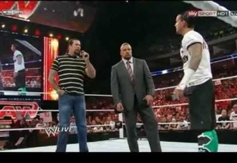 Kevin Nash and CM Punk face off while the COO looks on