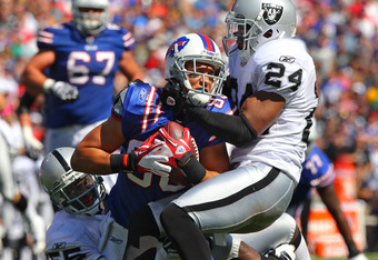 ORCHARD PARK, NY - SEPTEMBER 18: David Nelson #86 of the Buffalo Bills is tackled during an NFL game by Michael Huff #24 of the Oakland Raiders and Rolando McClain #55 at Ralph Wilson Stadium on September 18, 2011 in Orchard Park, New York. (Photo by Tom