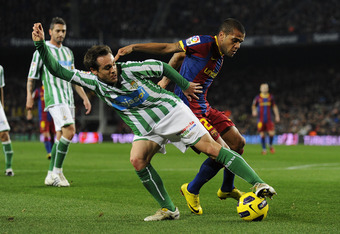 BARCELONA, SPAIN - JANUARY 12:  Dani Alves of FC Barcelona (L) duels for the ball against Nacho of Betis uring the Copa del Rey quarter final first leg match FC Barcelona and Betis at Camp Nou on January 12, 2011 in Barcelona, Spain. Barcelona won 5-0.  (