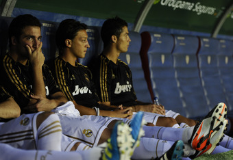 VALENCIA, SPAIN - SEPTEMBER 18:  Gonzalo Higuain (L), Mesut Ozil (C) and Cristiano Ronaldo of Real Madrid look on from the bench prior the La Liga match between Levante UD and Real Madrid CF at Ciutat de Valencia Stadium on September 18, 2011 in Valencia,