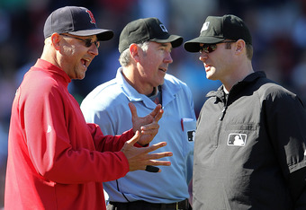 Red Sox manager Terry Francona pleads his case with umpires Mike Estabrook (R) and Mike Winters