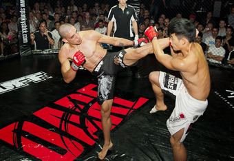 Adam Kayoom (black shorts) attempts a head kick against Seok Mo Kim. Photo by Marcel Braendli.