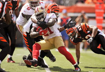 CINCINNATI, OH - SEPTEMBER 25:  Frank Gore #21 of the San Francisco 49ers is brought down by Carlos Dunlap #96 of the Cincinnati Bengals after a short gain in the first half at Paul Brown Stadium on September 25, 2011 in Cincinnati, Ohio.  (Photo by Jamie
