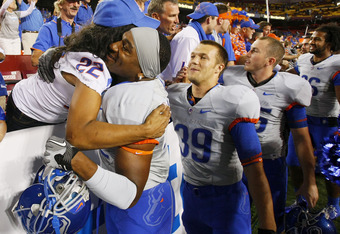 LANDOVER, MD - SEPTEMBER 06:  Linebacker #52 Derrell Acrey of the Boise State Broncos hugs a fan after the Broncos defeated the Virginia Tech Hokies 33-30 at FedExField on September 6, 2010 in Landover, Maryland.  (Photo by Geoff Burke/Getty Images)