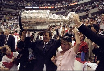 16 Jun 1998:  Team owners of the Detroit Red Wings Mike and Marian Ilitch hold the Stanley Cup trophy up over their heads during the Stanley Cup Finals game against the Washington Capitals at the MCI Center in Washington, D. C.. The Red Wings defeated the