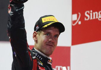 SINGAPORE - SEPTEMBER 25:  Sebastian Vettel of Germany and Red Bull Racing celebrates on the podium after winning the Singapore Formula One Grand Prix at the Marina Bay Street Circuit on September 25, 2011 in Singapore.  (Photo by Mark Thompson/Getty Imag