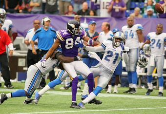 MINNEAPOLIS, MN - SEPTEMBER 25:  Michael Jenkins #84 of the Minnesota Vikings fumbles the ball after being hit by  Eric Wright #21 and  Stephen Tulloch #55 of the Detroit Lions at the Hubert H. Humphrey Metrodome on September 25, 2011 in Minneapolis, Minn