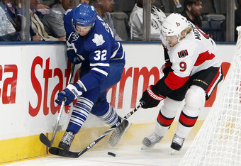 TORONTO, CANADA - SEPTEMBER 19: Joe Colborne #32 of the Toronto Maple Leafs moves the puck past Milan Michalek #9 of the Ottawa Senators during preseason NHL action at the Air Canada Centre September 19, 2011 in Toronto, Ontario, Canada. (Photo by Abelima