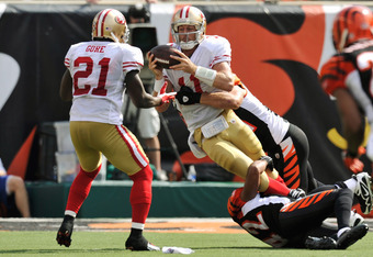 CINCINNATI, OH - SEPTEMBER 25:  Quarterback Alex Smith #11 of the San Francisco 49ers attempts to hand off to Frank Gore #21 of the San Francisco 49ers as he is being sacked by Chris Crocker #42 of the Cincinnati Bengals and Dan Skuta #51 of the Cincinnat