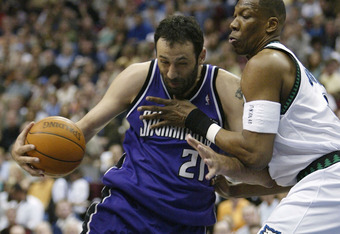 MINNEAPOLIS - MAY 8:  Vlade Divac #21 of the Sacramento Kings drives around Ervin Johnson #40 of the Minnesota Timberwolves in Game 2 of the NBA Western Conference Semifinals May 8, 2004 at the Target Center  in Minneapolis, Minnesota.  NOTE TO USER: User