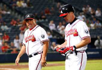 ATLANTA, GA - SEPTEMBER 12:  Fredi Gonzalez #33 and Chipper Jones #10 of the Atlanta Braves walk off the field after Jones beat out a ground ball in a collision at first base against Gaby Sanchez #15 of the Florida Marlins at Turner Field on September 12,