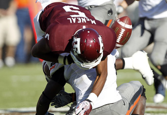 COLLEGE STATION, TX - SEPTEMBER 24:  Safety Daytawion Lowe #8 of the Oklahoma State Cowboys lays his helmet on the ball causing wide receiver Kenric McNeil #5 of the Texas A&M Aggies to fumble the ball in the third quarter at Kyle Field on September 24, 2