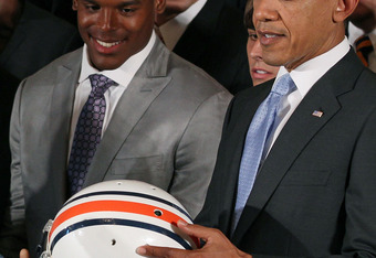 WASHINGTON, DC - JUNE 08: President Barack Obama (R) holds an Auburn Tigers helmet given to him by members of the 2011 BCS National Champion Auburn University football team including Heisman Trophy winner Cameron 'Cam' Newton in the East Room at the White