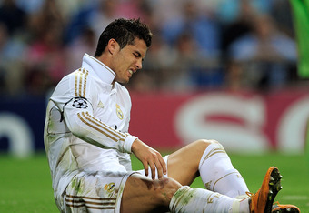 MADRID, SPAIN - SEPTEMBER 27: Cristiano Ronaldo of Real Madrid reacts after taking a knock during the UEFA Champions League Group D match between Real Madrid and AFC Ajax at Estadio Santiago Bernabeu on September 27, 2011 in Madrid, Spain.  (Photo by Deni