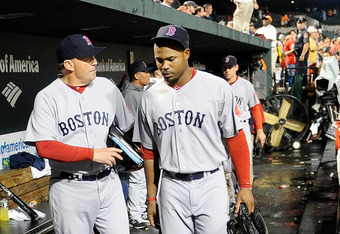 BALTIMORE, MD - SEPTEMBER 28: Carl Crawford #13 of the Boston Red Sox walks in the dugout with first base coach Ron Johnson #50 after a 4-3 loss against the Baltimore Orioles at Oriole Park at Camden Yards on September 28, 2011 in Baltimore, Maryland.  (P