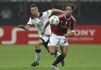 MILAN, ITALY - SEPTEMBER 28:  Luca Antonini of AC Milan is challenged by Milan Petrzela of Viktoria Plzen during the UEFA Champions League group H match between AC Milan and FC Viktoria Plzen at Giuseppe Meazza Stadium on September 28, 2011 in Milan, Ital