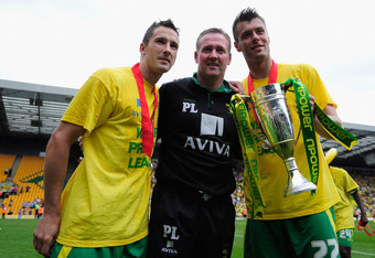 NORWICH, ENGLAND - MAY 07:  Manager of Norwich City Paul Lambert, Adam Drury and Elliot Ward celebrates promotion during the npower Championship match between Norwich City and Coventry City at Carrow Road on May 7, 2011 in Norwich, England.  (Photo by Jam