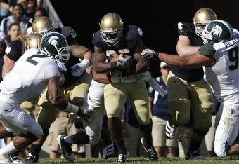 SOUTH BEND, IN - SEPTEMBER 17:  Jonas Gray #25 of the Notre Dame Fighting Irish rushes William Gholston #2 of the Michigan State Spartans during the first half September 17, 2011at Notre Dame Stadium in South Bend, Indiana. Notre Dame defeated Michigan St