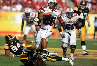 TAMPA, FL - JANUARY 01:  Eric Baker #28 of the South Carolina Gamecocks runs upfield past the tackle of Brett Greenwood #30 of the Iowa Hawkeyes during the Outback Bowl on January 1, 2009 at Raymond James Stadium in Tampa, Florida.  (Photo by Scott Haller