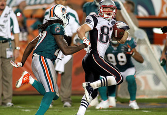 MIAMI GARDENS, FL - SEPTEMBER 12:  Receiver Wes Welker #83 of the New England Patriots catcges a pass against defensive back Bennie Sapp #27 of the Miami Dolphins at Sun Life Stadium on September 12, 2011 in Miami Gardens, Florida.  (Photo by Marc Serota/