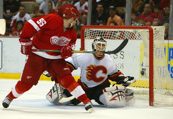 DDETROIT - APRIL 21:  Tomas Holmstrom #96 of the Detroit Red Wings provides a screen in front of Mikka Kiprusoff #34 of the Calgary Flames to allow a goal by Henrik Zetterberg #40 (not pictured) during game 5 of the 2007 NHL Western Conference Quarterfina