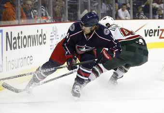 COLUMBUS, OH - SEPTEMBER 29:  David Savard #44 of the Columbus Blue Jackets chases the puck in the corner against Guillaume Latendresse #48 of the Minnesota Wild during their game on September 29, 2011 at Nationwide Arena in Columbus Ohio.  The Blue Jacke