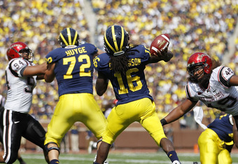 ANN ARBOR, MI - SEPTEMBER 24: Denard Robinson #16 of the Michigan Wolverines drops back to pass as Jerome Long #94 and J. J. Autele #49 of San Diego State rush during the game at Michigan Stadium on September 24, 2011 in Ann Arbor, Michigan. Michigan defe