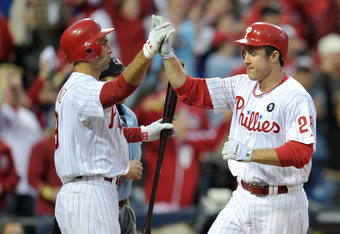 PHILADELPHIA, PA - OCTOBER 01:  (R-L) Chase Utley #26 of the Philadelphia Phillies is congratulated by Raul Ibanez #29 after scoring on a hit by Shane Victorino #8 in the fourth inning of Game One of the National League Division Series at Citizens Bank Pa