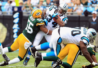 CHARLOTTE, NC - SEPTEMBER 18:   Desmond Bishop #55 of the Green Bay Packers tackles  DeAngelo Williams #34 of the Carolina Panthers during their game at Bank of America Stadium on September 18, 2011 in Charlotte, North Carolina.  (Photo by Streeter Lecka/