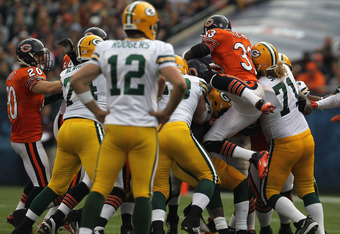 CHICAGO, IL - SEPTEMBER 25: Charles Tillman #33 of the Chicago Bears leaps on a pile stopping James Starks of the Green Bay Packers as Aaron Rodgers #12 watches at Soldier Field on September 25, 2011 in Chicago, Illinois. The Packers defeated the Bears 27