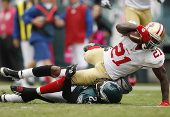 PHILADELPHIA, PA - OCTOBER 2: Running back Frank Gore #21 of the San Francisco 49ers drags cornerback Asante Samuel #22 of the Philadelphia Eagles into the end zone as he scores a touchdown during an NFL football game at Lincoln Financial Field on October