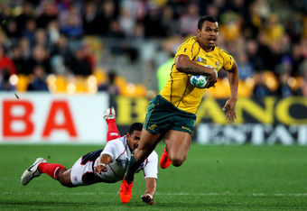 WELLINGTON, NEW ZEALAND - SEPTEMBER 23:  Kurtley Beale of the Wallabies  goes through the tackle from Tai Enosa of the USA during match 23 of the IRB 2011 Rugby World Cup between Australia and the USA at Wellington Regional Stadium on September 23, 2011 i