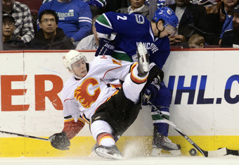 VANCOUVER, CANADA - JANUARY 5: Matt Stajan #18 of the Calgary Flames falls to the ice while trying to check Dan Hamhuis #2 of the Vancouver Canucks during the third period in NHL action on January 05, 2011 at Rogers Arena in Vancouver, BC, Canada.  (Photo