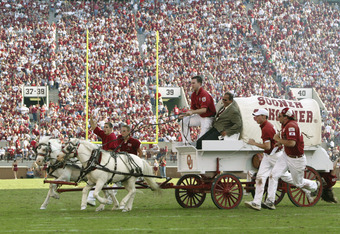 NORMAN, OK - SEPTEMBER 20:  Sideline reporter Jack Arute takes a ride on the University of Oklahoma Sooners Boomer Schooner after a touchdown during a game against the University of California, Los Angeles Bruins at Memorial Stadium on September 20, 2003