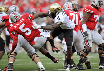 COLUMBUS, OH - SEPTEMBER 24:  Chidera Uzo-Diribe #9 of the Colorado Buffaloes throws down quarterback Braxton Miller #5 of the Ohio State Buckeyes after Miller made a completion in the second half at Ohio Stadium on September 24, 2011 in Columbus, Ohio. U